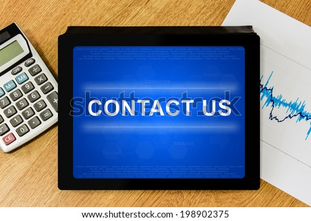 contact us word on digital tablet with calculator and financial graph - stock photo