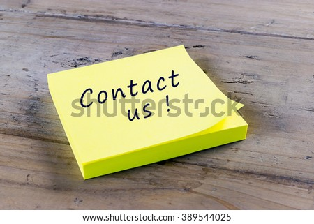 Contact us! Written on yellow sticky note. - stock photo