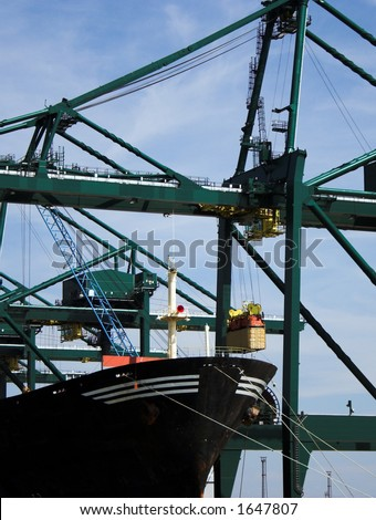 Container being transferred into a cargo ship at Antwerp harbor (brand names and logos have been removed) - stock photo