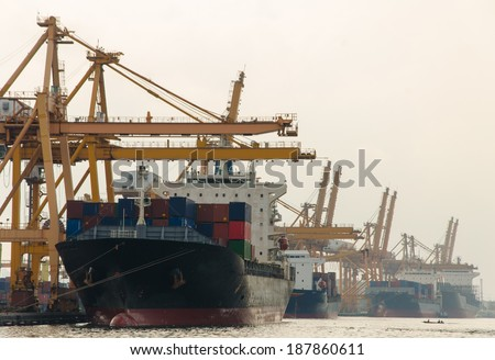 Container Cargo freight ship with working crane bridge in shipyard.