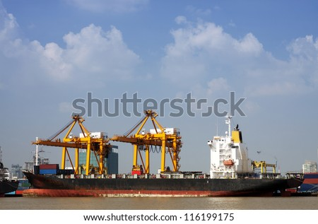 Container Cargo freight ship with working crane bridge in shipyard at dusk for Logistic Import Export background with blue sky