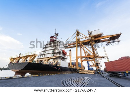 Container Cargo freight ship with working crane loading bridge in shipyard with Blue Sky at Logistic Import Export Zone background - stock photo