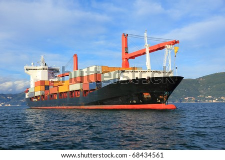 container cargo ship arriving in harbor - stock photo
