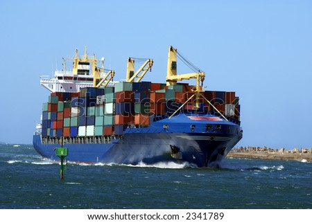 Container cargo ship going into port - stock photo