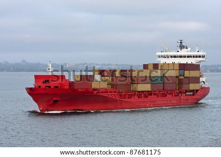 Container cargo ship in red, at sea.