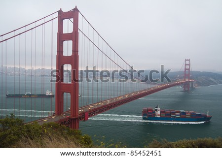 Container cargo ship passing underneath Golden Gate bridge - stock photo