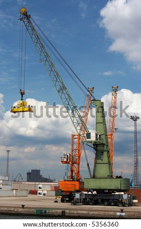 Container crane going down to grab one more container and carry it into a ship (all brand names and logos have been carefully removed) - stock photo