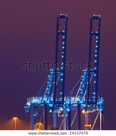 Container cranes in the Port of Rotterdam against purple night sky - stock photo
