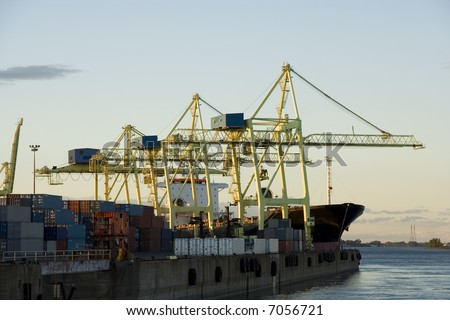 Container cranes loading a ship in a major port - stock photo