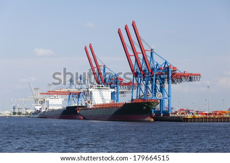 Container harbor with tall cranes and docked ships in Hamburg Harbor, Germany - stock photo