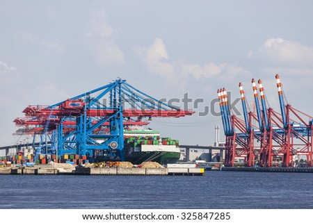 Container harbor with tall cranes in Hamburg Harbor, Germany