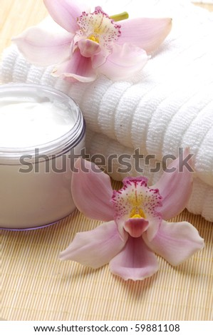 container of cosmetic moisturizing cream with pink orchids with towel