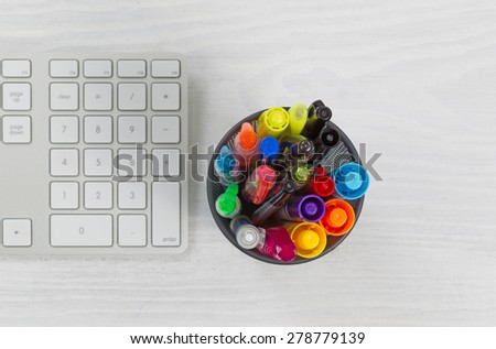 Container of pens and markers, focus top of container, and computer keyboard on rustic white desktop.  - stock photo