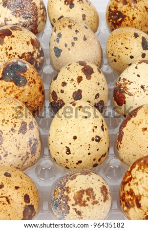Container of quail eggs on light background, food photo