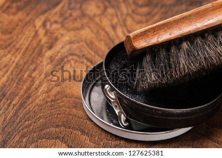 container of shoe polish and brush on wooden background - stock photo