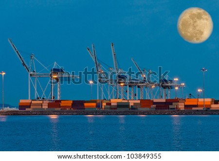 Container port terminal at night ( dawn, dick ) time with big moon in the sky. - stock photo