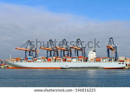container ship and harbor cranes in the port of rotterdam netherlands - stock photo