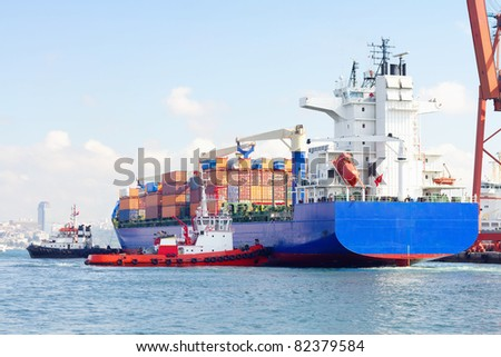 Container ship and tug boats - stock photo