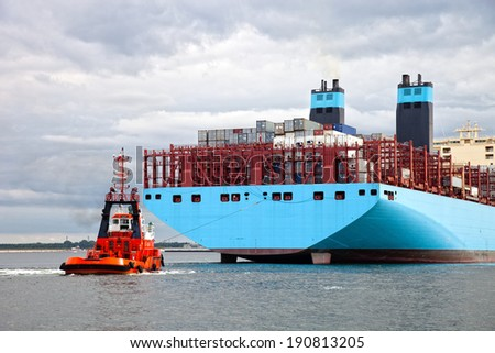 Container ship arriving at port, assisted by tugboat. - stock photo