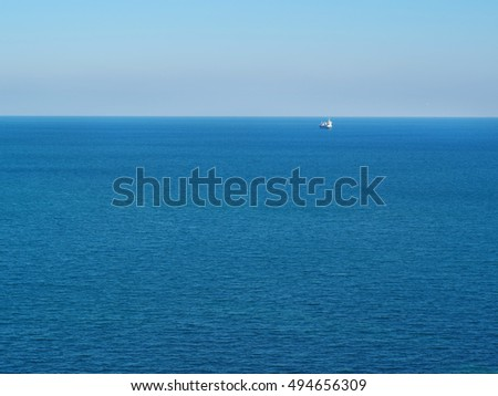 Container ship at anchor on the horizon