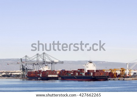 Container ship at port, being unloaded