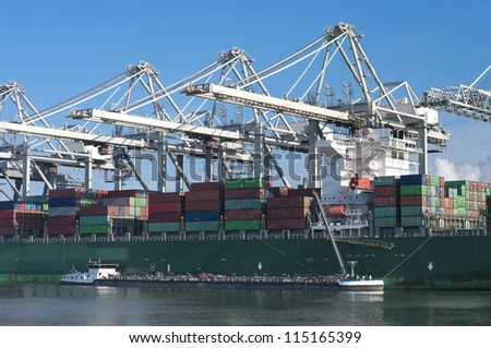 container ship being unloaded and refueled in Rotterdam harbor - stock photo