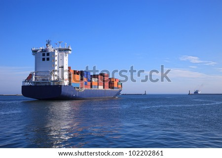 Container ship departs from a port in the sea. - stock photo