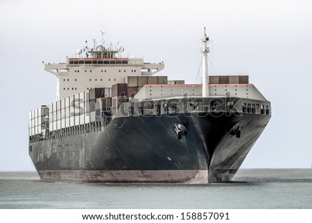 container ship entering the port of antwerp - stock photo