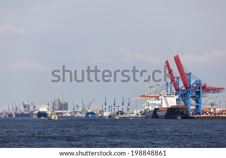 Container ship in Hamburg Harbor, Germany with the city skyline in the background - stock photo