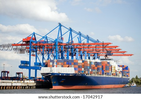 container ship in port terminal - huge freighter fully loaded - stock photo