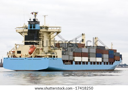 container ship sailing into port - stock photo