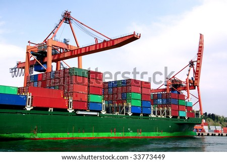 Container ship under loading on an industrial harbor - stock photo