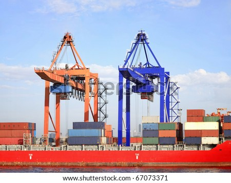 Container ship under twin cranes at harbor - stock photo