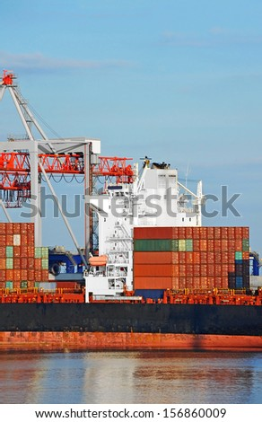Container stack and cargo ship under crane bridge