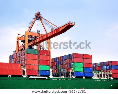 Container stacks on board under crane bridge - stock photo