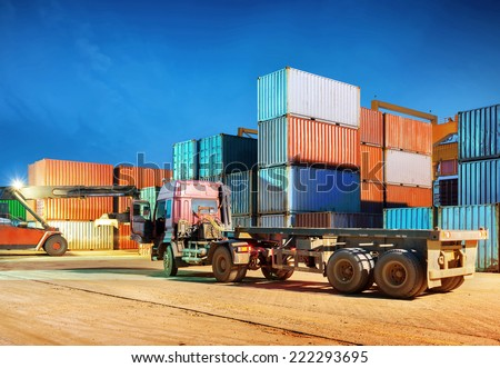 Container terminal at night, stopped working forklifts and trucks. - stock photo