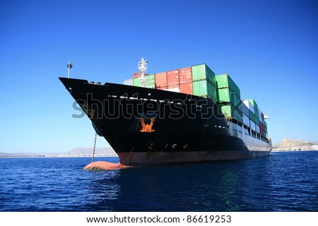 Container transport ship, anchored in the bay of Alicante. - stock photo