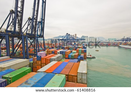 container vessel and a small tug boat - mooring operations in Hong Kong - stock photo