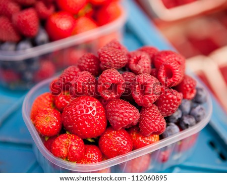 container with a fruit platter raspberries strawberries blueberries - stock photo