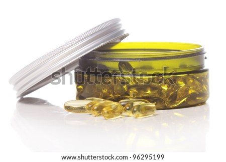 Container with gelatin capsules over white background - stock photo