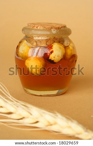 Container with honey and dry fruits and tenon of wheat - stock photo