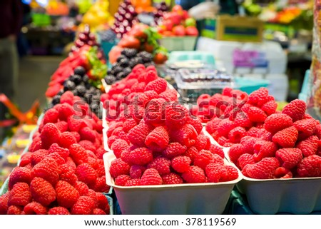Containers of fresh raspberries on display in a Canadian grocery store - stock photo