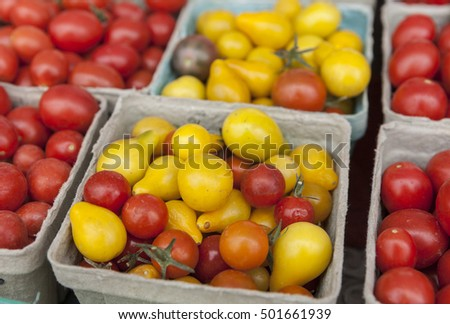 Containers of red and yellow cherry tomatoes on display.