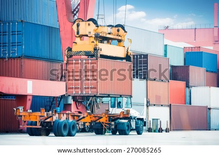 containers storage area , cargo freight truck and industrial crane closeup