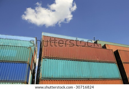 Containers waiting to be loaded against a clear blue sky with one white cloud. No names on the containers