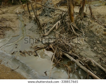 Contaminated water and land caused by chronic carcinogenic crude oil pollution at an illegal oil field in East Java, Indonesia. - stock photo