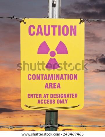 Contamination area warning sign with orange sunrise. - stock photo