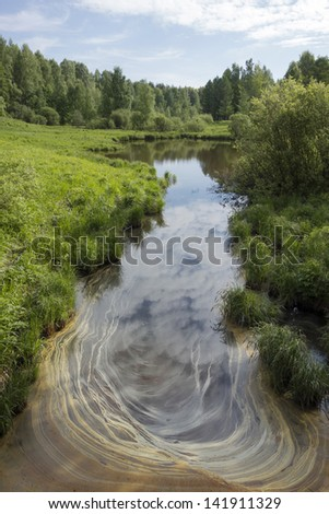 Contamination of a small river in the forest - stock photo