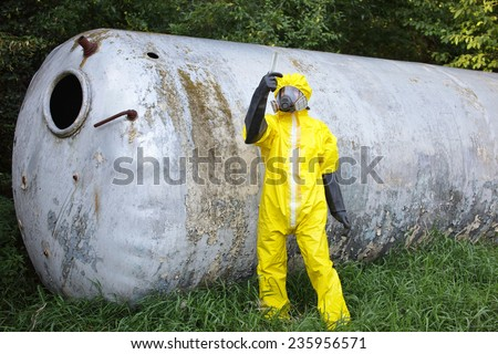 contamination - technician in protective coveralls ,mask, and gloves examining sample from large stainless tank - stock photo