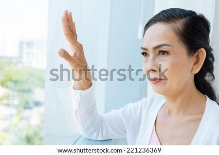 Contemplating Asian aged woman looking out of the window - stock photo